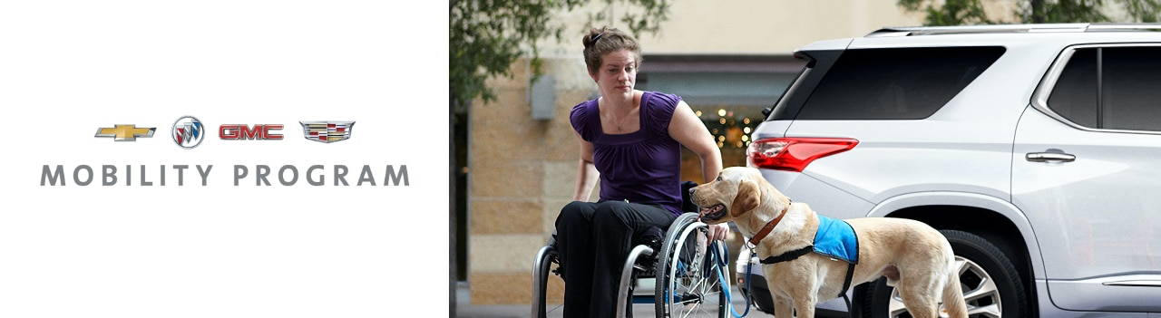 Mobility Program. Woman in wheelchair with a guide dog in front of a vehicle.